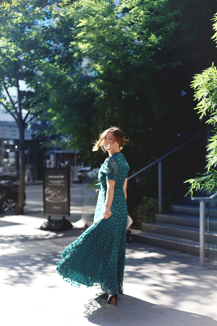 To Vogue or Bust shares what to wear to a black tie wedding in a green dotted Revole Tularosa dress, Ted Baker pink clutch and a low chignon.