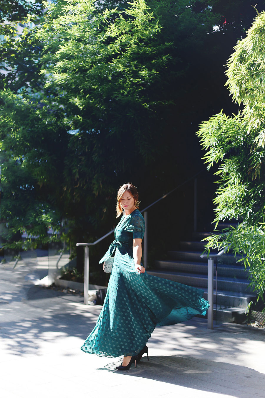 To Vogue or Bust shares what to wear to a black tie wedding in a green dotted Revole Tularosa dress, Ted Baker pink clutch, Leah Alexandra rings and Swarovski rings, and a low chignon.