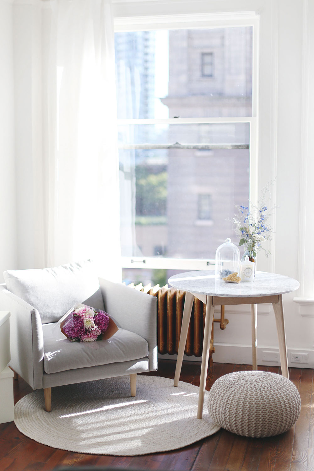 Airy studio space decor tips with marble coffee table, grey minimalist armchair, jute rug and Moroccan pouf by Article furniture