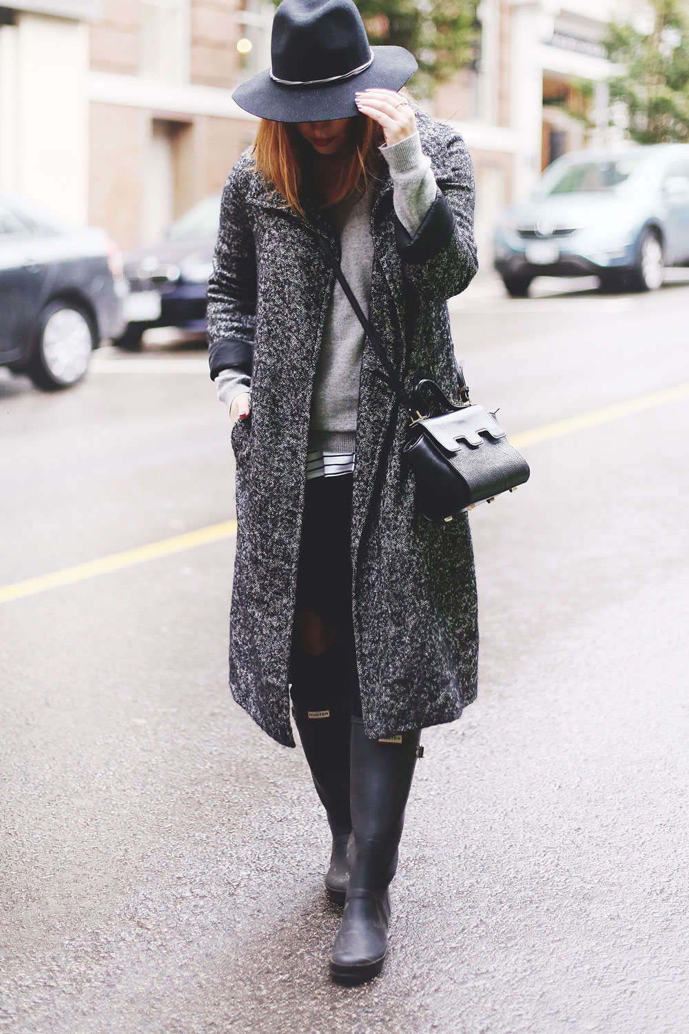 Rainy day outfit ideas for fall, featuring Aritzia Babaton wool trench coat, White and Warren cashmere sweater, striped tank top, Express black wool fedora, Mezzi Mini Cosma bag, Hunter rain boots