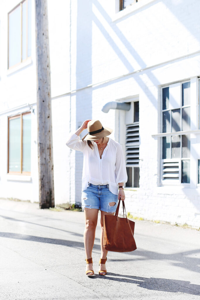 Denim cut-offs, white blouse, floppy hat, leather tote.