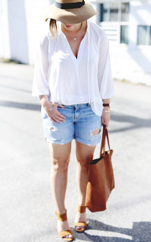 Denim boyfriend cut-off shorts, suede heels, oversized leather tote, sheer white blouse, floppy tan hat.