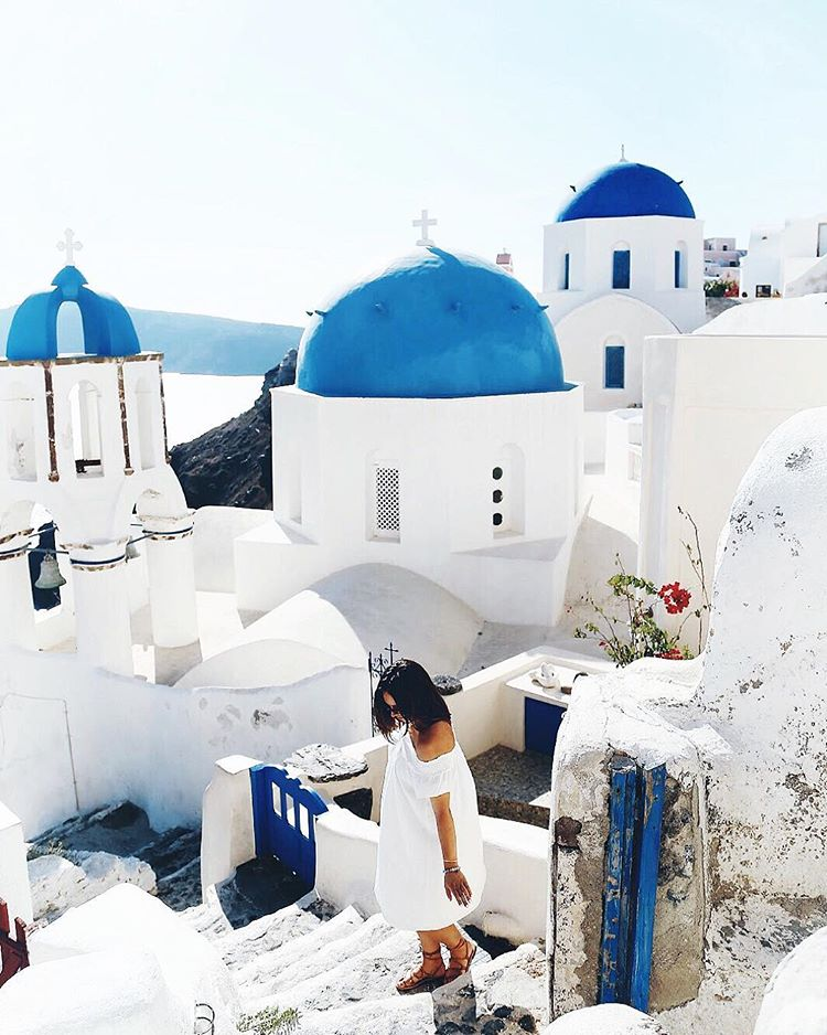 To Vogue or Bust wearing Aritzia off the shoulder dress in Oia, Santorini, Greece
