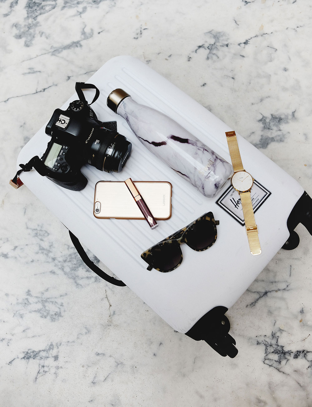 To Vogue or Bust shares how to beat jet lag in CLUSE gold mesh watch, Free People cardigan, Mavi black skinny jeans, Aritzia white silk camisole, Urban Outfitters suede ankle boots, Herschel Supply white carry-on luggage, Swell marble bottle, Logix case, Bailey Nelson sunglasses