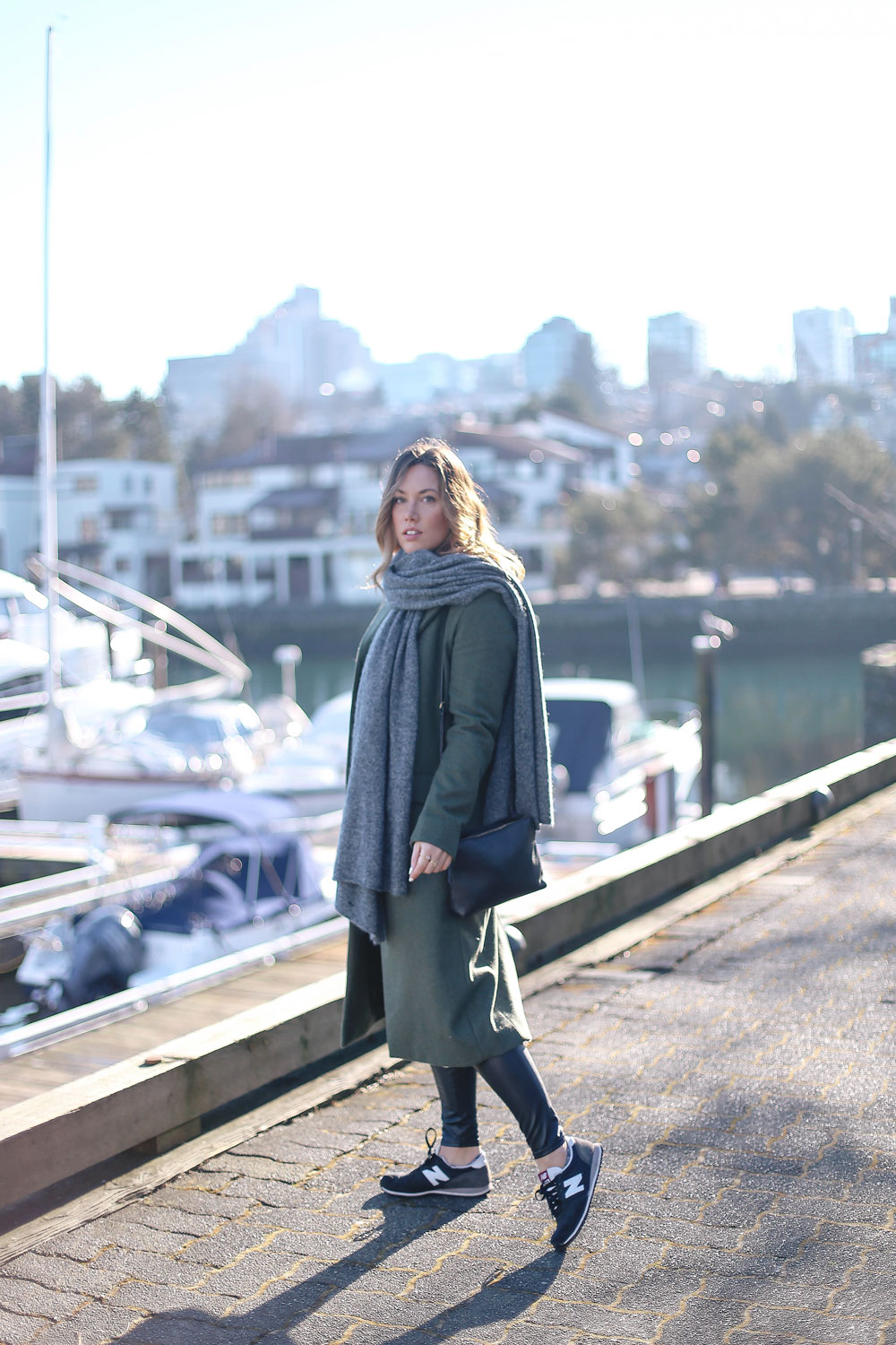 Tips to style sneakers in New Balance sneakers, a statement green coat, leather leggings and cashmere cardigan