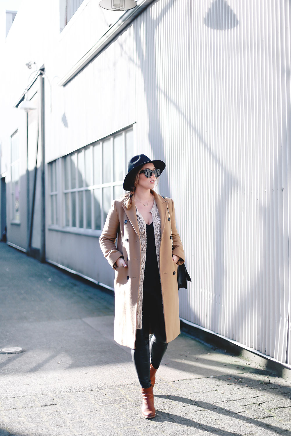 Best winter to spring transition piece in a camel wool coat, leather leggings, leopard cross body bag, statement vest and wool fedora