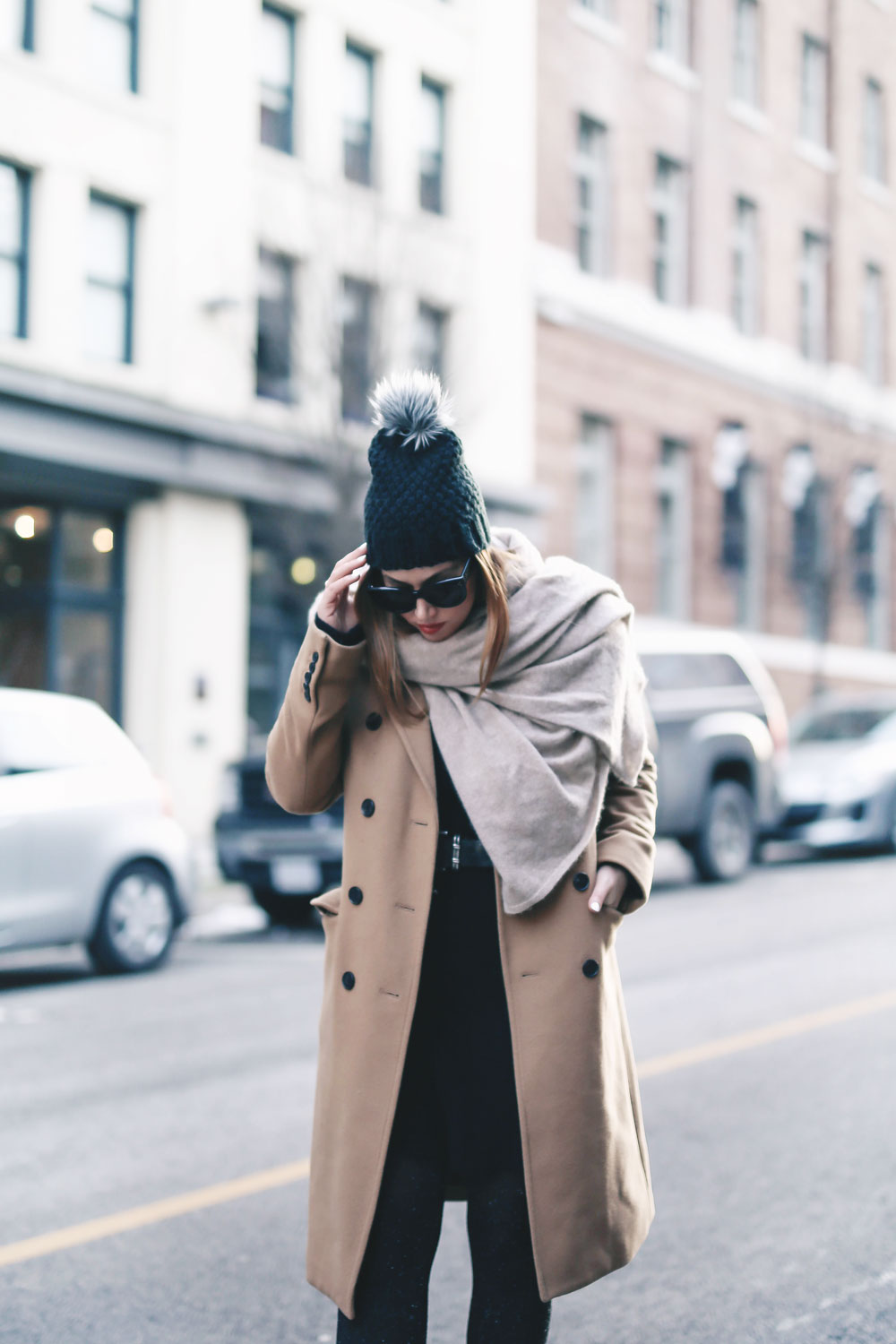 Tips on wearing a dress in the winter styled by To Vogue or Bust in an Aritzia camel wool coat, White and Warren cashmere dress, White and Warren cashmere travel wrap, Frye ankle boots, Express beanie hat and Celine Caty sunglasses