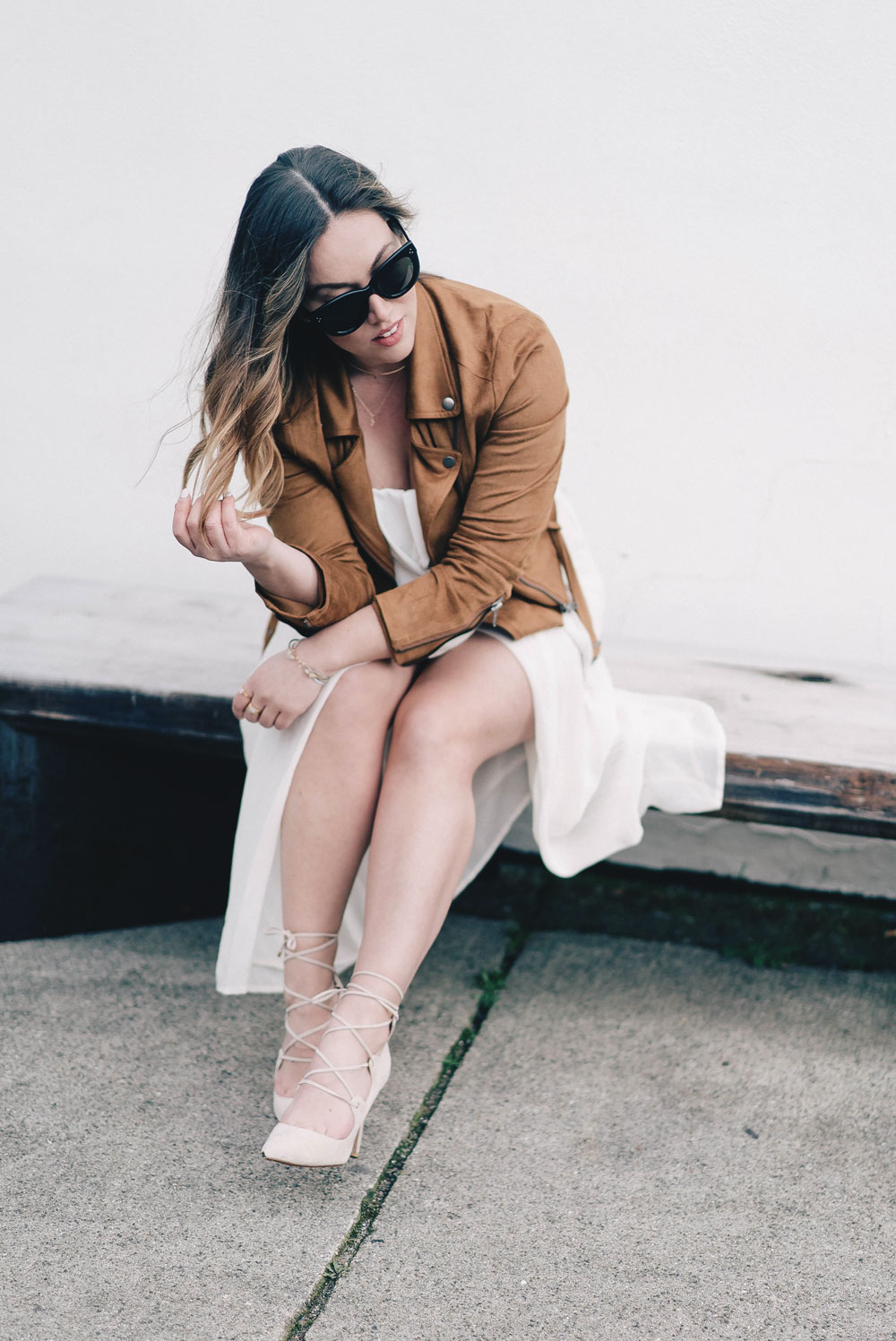 Western trend style tips in Lovers + Friends suede jacket, Revolve clothing, Aritzia skirt, Chicwish cropped top, Raye heels, Bega bag, Leah Alexandra jewelry, Celine sunglasses styled by To Vogue or Bust