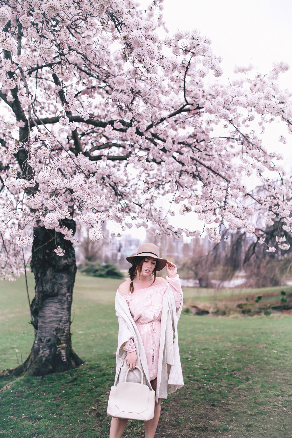 How to style off the shoulder spring trend in Revolve dress, Express wool fedora, Leah Alexandra jewellery, Revolve strapless dress, Mavi Coatigan, Lovers and Friends dress, how to wear strapless, cherry blossoms in Vancouver by To Vogue or Bust