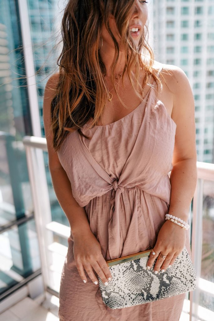 An easy go-to wedding look; a flowy dress that hits below the knee, nude pumps, and a fun clutch, styled by To Vogue or Bust!